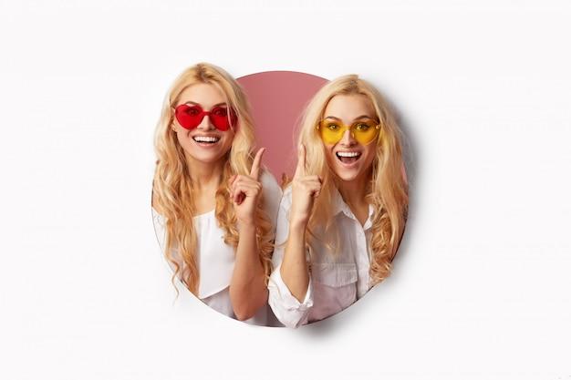 Portrait de deux jeunes femmes heureuses et choquées dans les lunettes de soleil en forme de coeur à travers le trou blanc dans le mur. grande vente. visages amusants. espace vide pour le texte