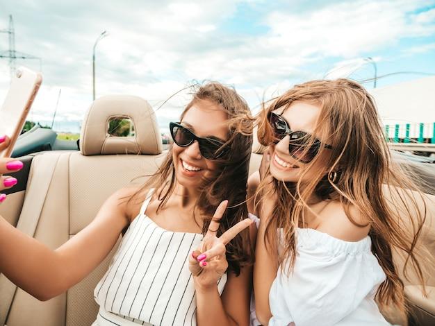 Portrait de deux jeunes femmes hipster belle et souriante en voiture décapotable