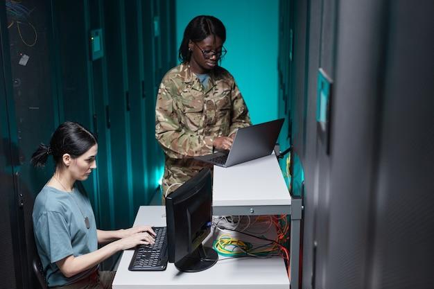 Portrait de deux jeunes femmes militaires utilisant des ordinateurs tout en travaillant ensemble dans la salle des serveurs et en mettant en place un réseau