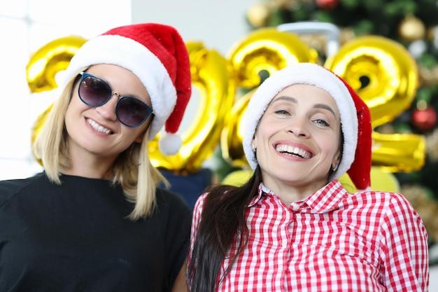 Portrait de deux jeunes femmes souriantes sur fond d'arbre de noël et de chiffres