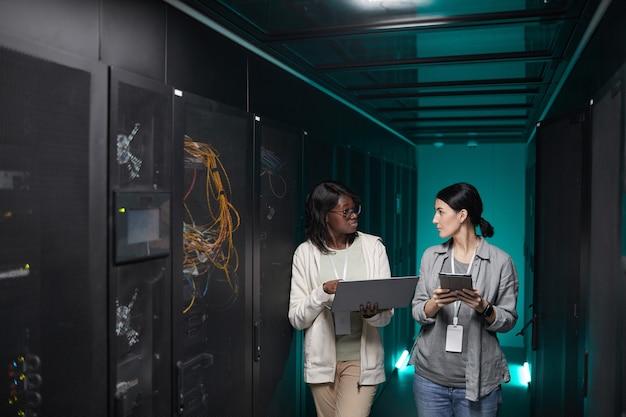 Portrait de deux jeunes femmes utilisant un ordinateur portable dans la salle des serveurs lors de la configuration d'un réseau de superordinateurs, espace de copie