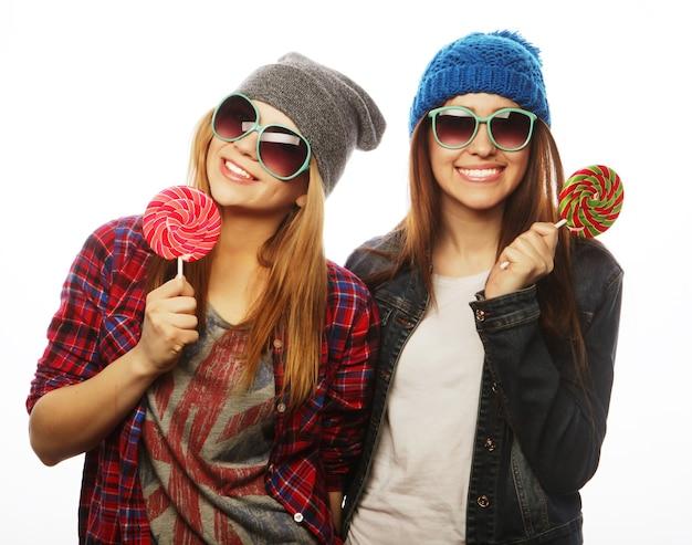 Portrait de deux jeunes filles assez hipster portant des chapeaux et des lunettes de soleil tenant des bonbons