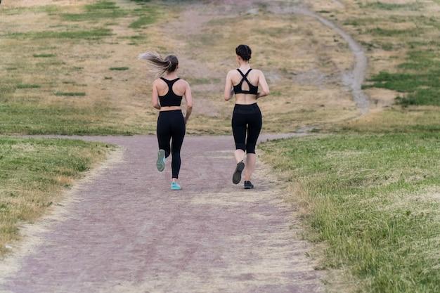 Portrait de deux jeunes filles élégantes en vêtements de sport noirs sont en cours d'exécution dans le parc à l'extérieur.