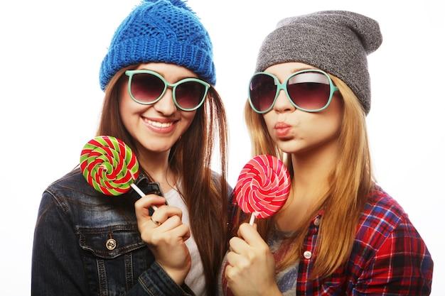 Portrait de deux jeunes filles jolies hipster portant des chapeaux et des lunettes de soleil tenant des bonbons.