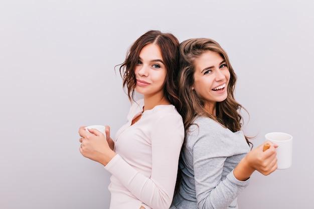 Portrait de deux jeunes filles en pyjama avec tasses sur mur gris. ils se tiennent dos à dos et sourient.