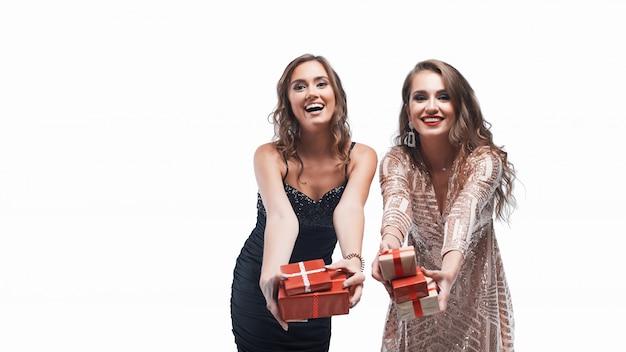 Portrait de deux jeunes filles vous donnant des cadeaux isolé sur blanc