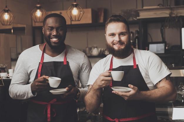 Portrait de deux jeunes hommes barista à l'espace de travail