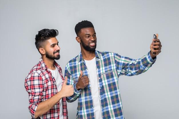Portrait de deux jeunes hommes excités prenant un selfie tout en se tenant ensemble isolé