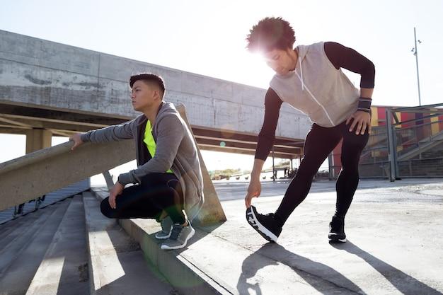 Portrait de deux jeunes hommes en forme et sportifs se relaxant et s'étirant après l'entraînement.