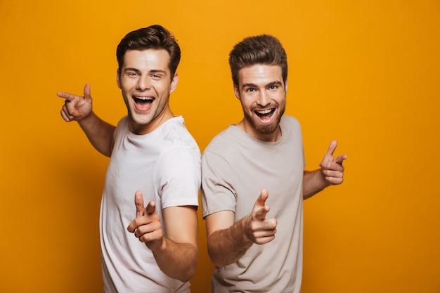 Portrait de deux jeunes hommes heureux meilleurs amis pointant du doigt