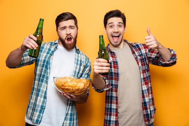 Portrait de deux jeunes hommes joyeux, boire de la bière