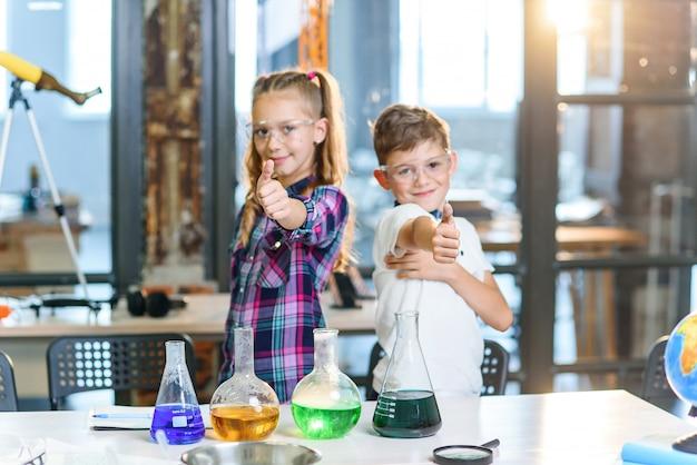 Portrait de deux jeunes scientifiques gais de race blanche dans des lunettes de sécurité montrant les pouces vers le haut en classe chimique de l'école primaire