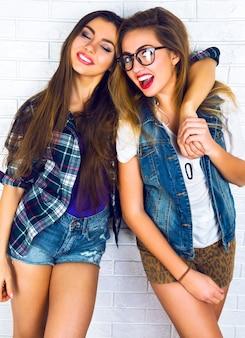 Portrait de deux jolies copines adolescentes souriant et se serrant dans leurs bras