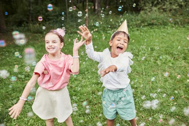 Portrait de deux jolies filles jouant avec des bulles tout en profitant d'une fête d'anniversaire à l'extérieur en été