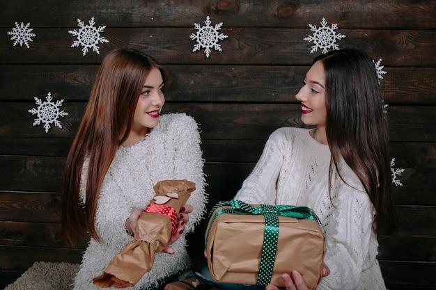 Portrait de deux jolies jeunes femmes avec des cadeaux de noël