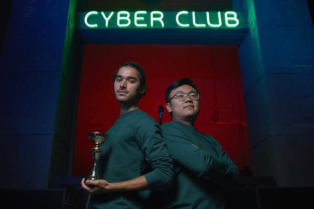 Portrait de deux joueurs debout dos à dos regardant la caméra et tenant la tasse après la compétition en jeu d'ordinateur