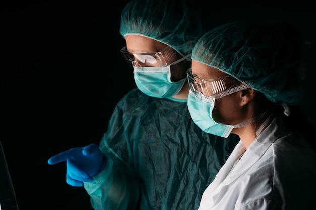 Portrait de deux médecins travaillant avec un masque chirurgical médical, un bonnet médical et des vêtements de protection contre les virus