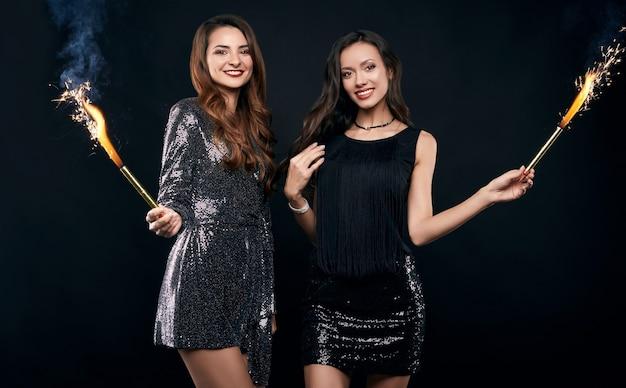 Portrait de deux meilleurs amis assez fous dans des robes de mode posant avec des feux d'artifice