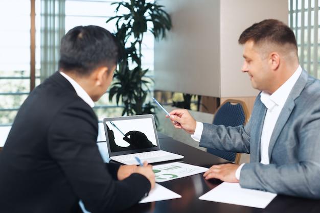 Portrait de deux partenaires commerciaux assis à une table ensemble et travaillant.