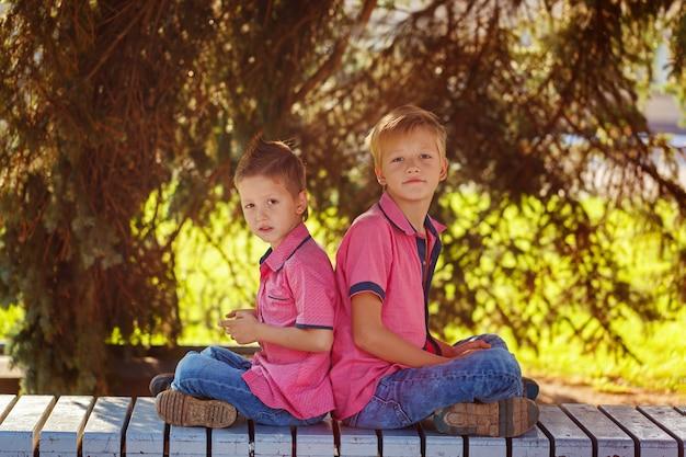 Portrait deux petits garçons jouant à des jeux sur téléphone portable sous le soleil