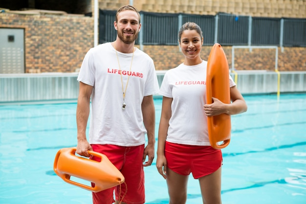 Portrait de deux sauveteurs debout avec bouée de sauvetage au bord de la piscine