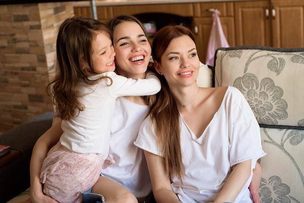 Portrait de deux soeurs et d'une petite fille assise sur le canapé, souriant. concept: famille, sœurs, foyer et bonheur.