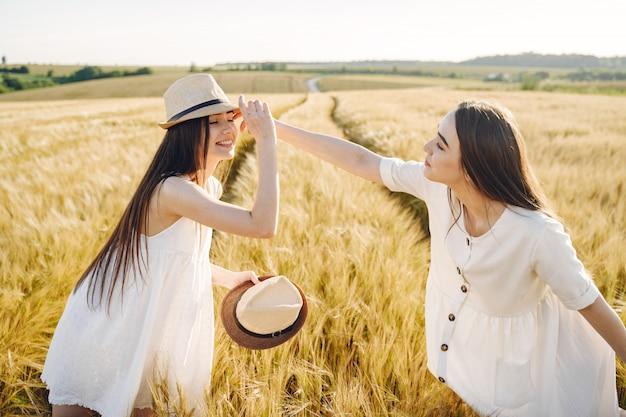 Portrait de deux sœurs en robes blanches aux cheveux longs dans un champ