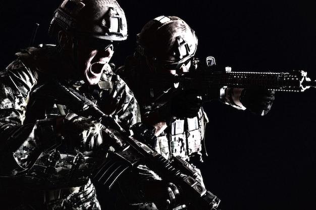 Portrait de deux soldats des forces spéciales en uniforme de campagne avec des armes attaquant en criant, portrait sur fond noir