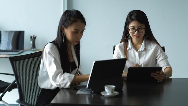Portrait de deux travailleuses consultant sur leur travail avec tablette dans la salle de réunion