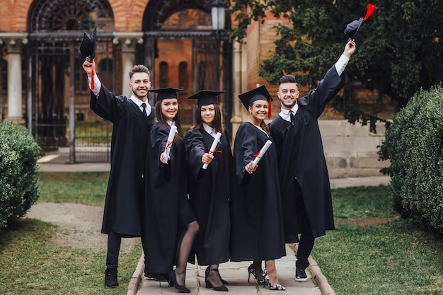 Portrait, diplômés, tenue, diplôme, sourire