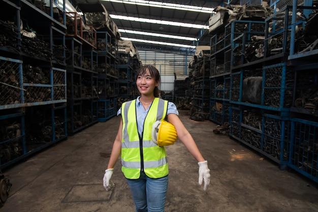 Portrait des directeurs d'entrepôt ou d'une travailleuse asiatique travaillant dans un grand entrepôt de distribution de pièces automobiles anciennes.