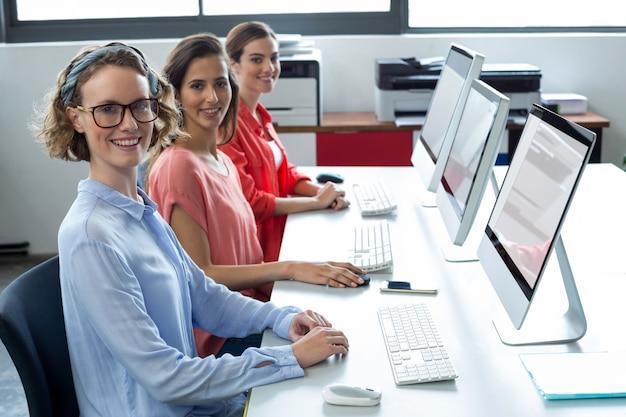 Portrait de dirigeants d'entreprise souriant travaillant sur ordinateur