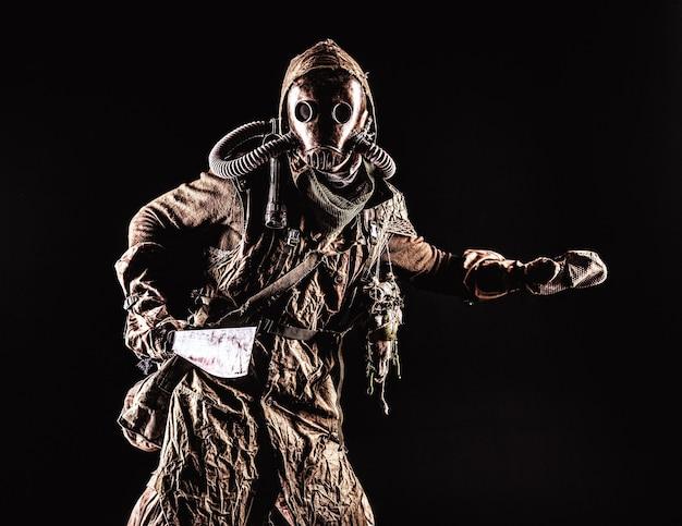 Portrait discret d'une créature post-apocalyptique, vivant dans des catacombes mutantes, a survécu à une catastrophe nucléaire humaine en tissu déchiqueté et masque à gaz, armé d'une arme froide faite à la main isolée sur fond noir