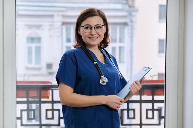 Portrait de docteur souriant mature avec presse-papiers stéthoscope