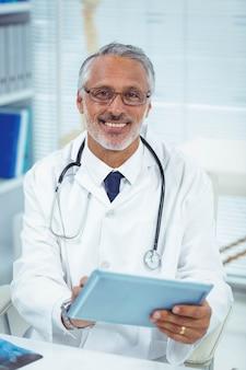Portrait, de, docteur souriant, utilisation, tablette numérique, à, clinique