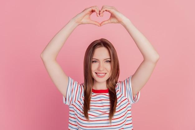 Portrait de doigts de belle dame romantique montrent le geste du coeur lever les bras sur fond rose