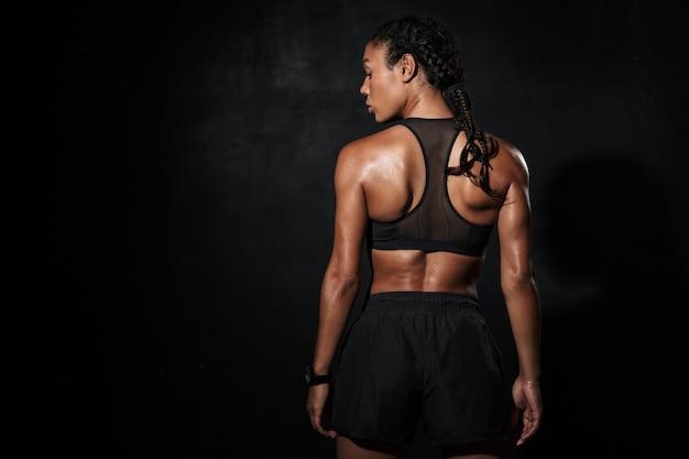 Portrait de dos d'une femme afro-américaine athlétique en tenue de sport debout isolée sur fond noir
