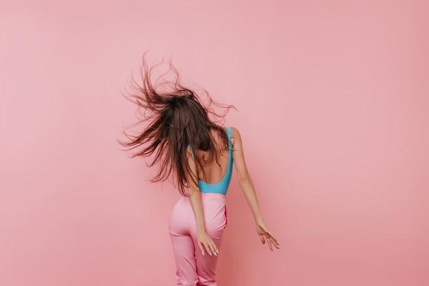 Portrait de dos de fille bronzée en débardeur bleu en agitant les cheveux longs