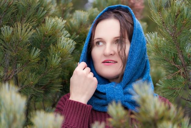 Portrait d'une douce femme brune aux yeux bruns et aux cheveux longs se dresse dans une forêt de sapins, regardant de côté