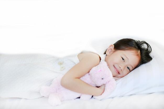 Portrait d'une douce petite fille asiatique souriante allongée sur le lit le matin en regardant la caméra.