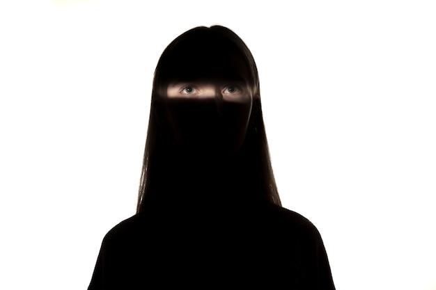 Portrait dramatique de jeune fille dans le noir isolé sur un mur de studio blanc
