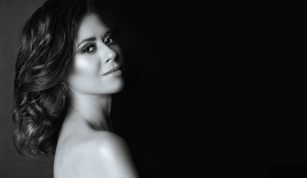 Portrait dramatique d'une superbe jeune femme aux épaules nues posant dans l'ombre. espace pour le texte