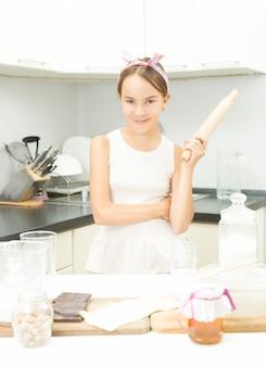 Portrait drôle d'une adolescente mignonne posant avec un rouleau à pâtisserie en bois dans la cuisine