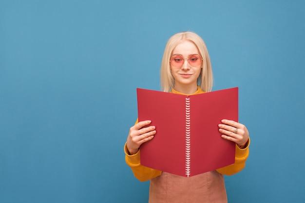 Portrait d'une drôle de blonde à lunettes roses sur un bleu, tient un cahier rouge dans ses mains et lit.