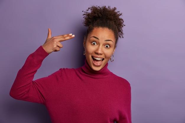 Portrait de drôle de femme aux cheveux bouclés positive fait un geste de suicide, tire dans le temple, rit joyeusement, fou autour, porte poloneck bordeaux, isolé sur mur violet, se tue