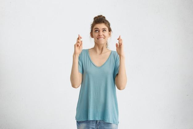 Portrait de drôle de femme brune aux yeux bleus, vêtu d'un t-shirt décontracté lâche levant les mains croisant les doigts et mordant la lèvre souhaitant avoir un miracle, espérant le meilleur et la bonne chance dans sa vie