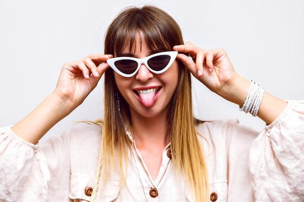 Portrait drôle fou de femme montrant une longue langue, faisant la grimace