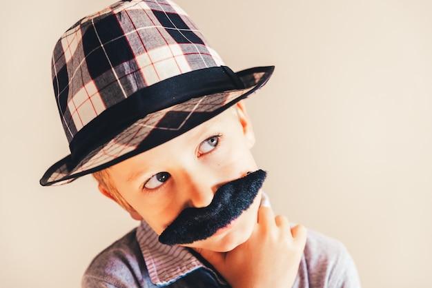 Portrait drôle de garçon pensif avec une fausse moustache et un chapeau