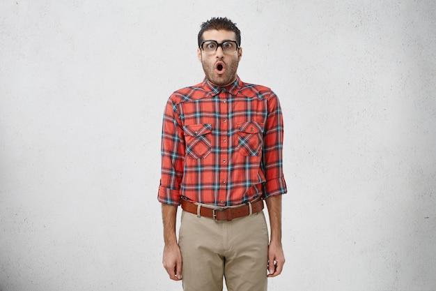 Portrait de drôle de geek masculin choqué voit quelque chose d'étonnant devant lui