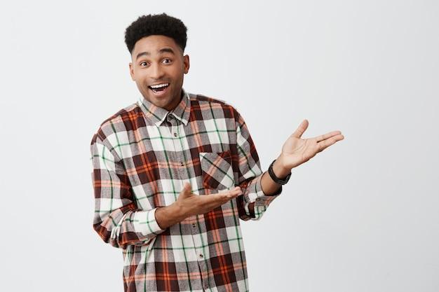 Portrait de drôle jeune bel homme à la peau foncée avec une coiffure afro en chemise décontractée souriant, montrant un mur blanc avec les mains avec une expression excitée et heureuse